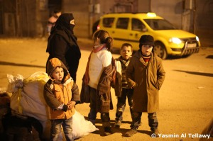 A mother cries with her children as they stand with their few belongings wondering where they can go.